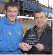 Jack Defty receives a trophy from Gordon Chilvers  to mark his 250 first team appearances for the club.